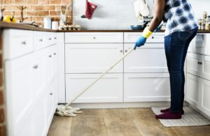 Woman mopping the kitchen floor.