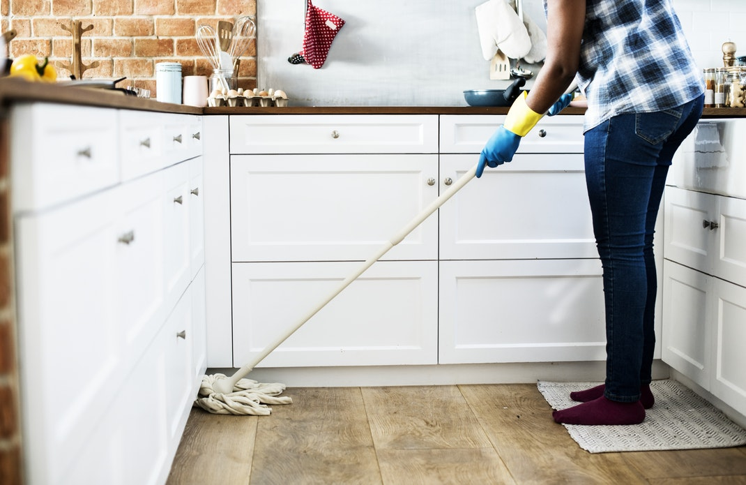 A woman mopping a floor.