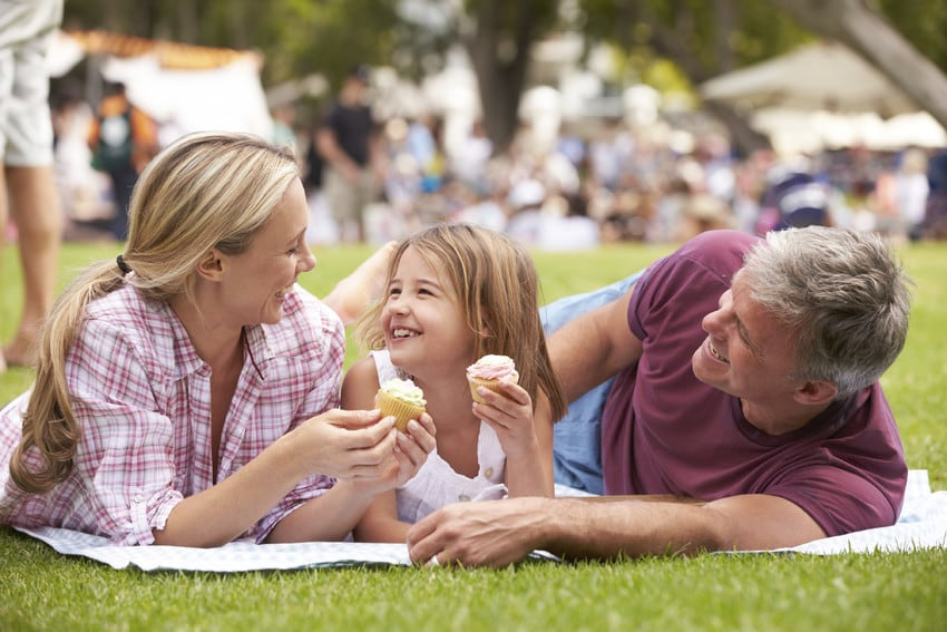 A happy family eating cupcakes on the lawn.