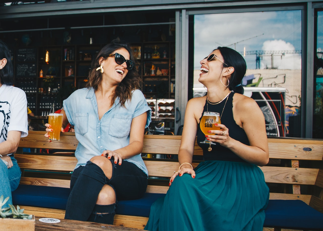 Two adult women laughing at a joke and drinking craft beer.