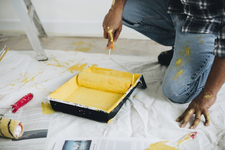 A man using a paint roller.