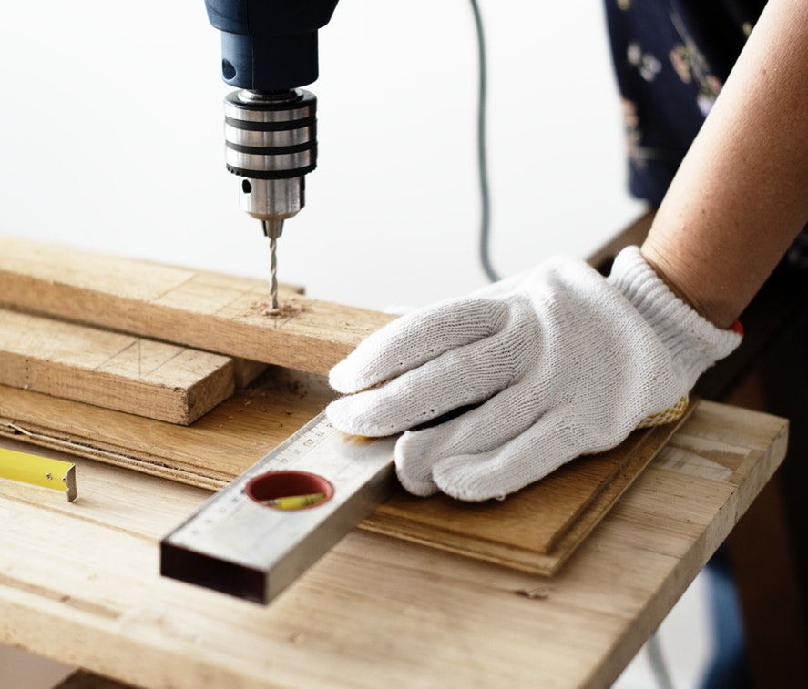 A person drilling into a wooden plank.