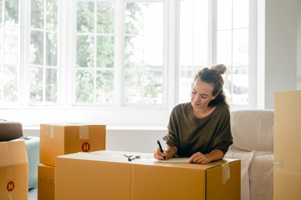 A woman packs up moving boxes.